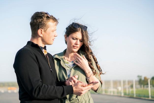 Młoda para mężczyzna i kobieta patrząc zdjęcie z wakacji, zabawy na świeżym powietrzu
