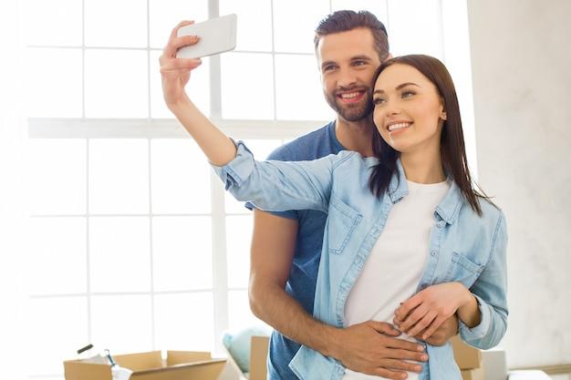 Młoda para mężczyzna i kobieta przeprowadza się razem do nowego mieszkania za pomocą urządzenia cyfrowego