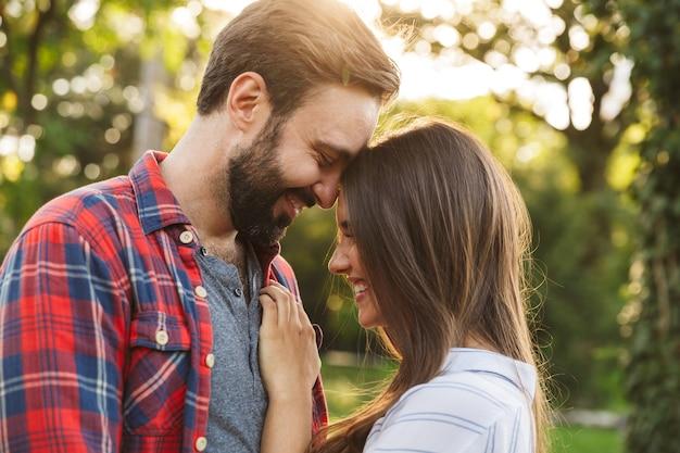 Młoda para mężczyzna i kobieta ubrani w codzienny strój przytulający się i uśmiechający się podczas spaceru po zielonym parku