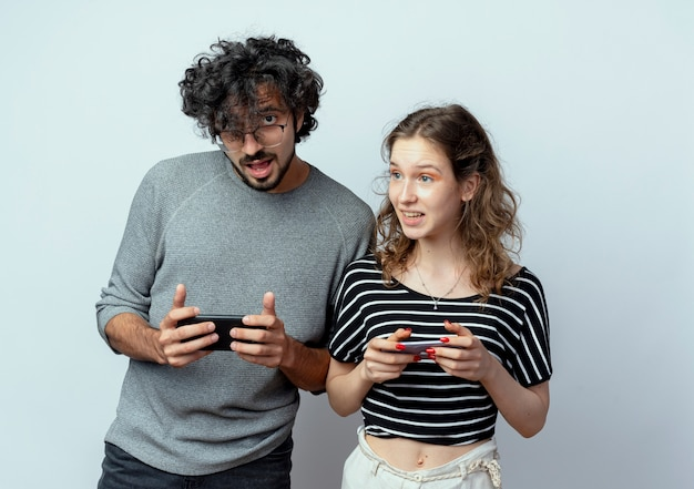 Młoda para mężczyzna i kobieta uśmiecha się, trzymając telefony komórkowe stojąc nad białą ścianą