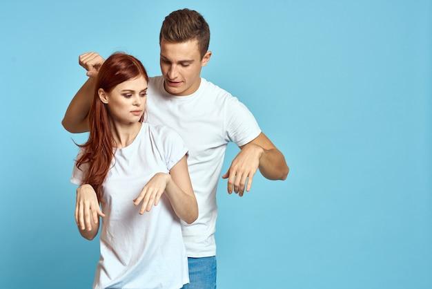 Młoda para mężczyzna i kobieta w białych koszulkach na jasnoniebieskiej przestrzeni