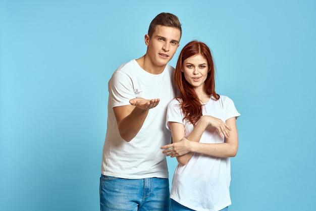 Młoda para mężczyzna i kobieta w białych koszulkach na jasnoniebieskim tle