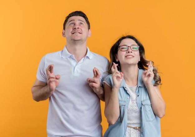 Młoda para mężczyzna i kobieta w ubranie patrząc w górę czyniąc pożądane życzenie krzyżując palce na pomarańczowo