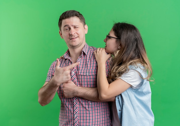 Młoda para mężczyzna i kobieta w ubranie pewny siebie mężczyzna wskazując palcem na swoją dziewczynę stojącą nad zieloną ścianą