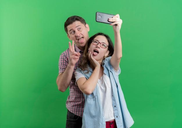 Młoda para mężczyzna i kobieta w ubranie stojących razem robi selfie szczęśliwy w miłości zabawy na zielonej ścianie