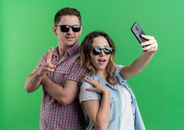 Młoda para mężczyzna i kobieta w ubranie stojących razem robi selfie szczęśliwy w miłości, zabawy na zielonej ścianie
