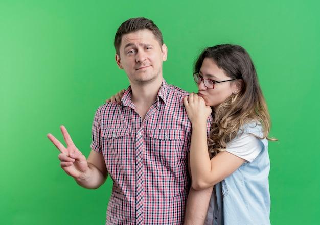 Młoda para mężczyzna i kobieta w ubranie stojących razem szczęśliwy człowiek pokazujący znak v na zielonej ścianie