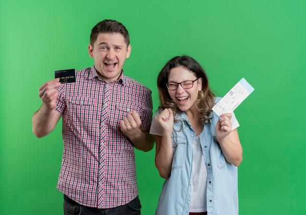 Młoda para mężczyzna i kobieta w ubranie szczęśliwy mężczyzna trzyma kartę kredytową, podczas gdy jego dziewczyna trzyma bilety lotnicze szczęśliwa i podekscytowana stojąc nad zieloną ścianą