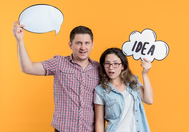 Młoda para mężczyzna i kobieta w ubranie, trzymając znaki dymku nad głowami uśmiechając się stojąc nad pomarańczową ścianą