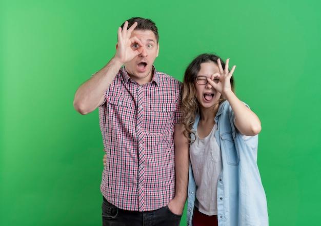 Młoda para, mężczyzna i kobieta w zwykłych ubraniach, robiąc znaki ok patrząc przez te znaki stojące nad zieloną ścianą