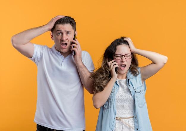Młoda para mężczyzna i kobieta w zwykłych ubraniach rozmawiają przez telefony komórkowe wyglądają na zdezorientowanych i bardzo zaniepokojonych dotykając głowami stojącymi nad pomarańczową ścianą