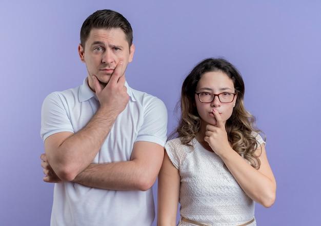 Młoda para mężczyzna i kobieta z rękami na brodach, myśląc stojąc nad niebieską ścianą