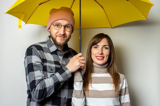 Młoda para, mężczyzna z brodą w kapeluszu i kraciastej koszuli oraz dziewczyna w swetrze uśmiechają się pod żółtym parasolem na odosobnionym świetle