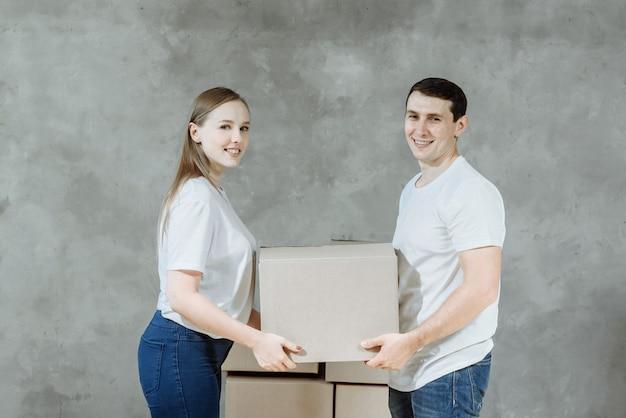Młoda para mężczyzny i kobiety posiadających pola do przeprowadzki w nowym domu.