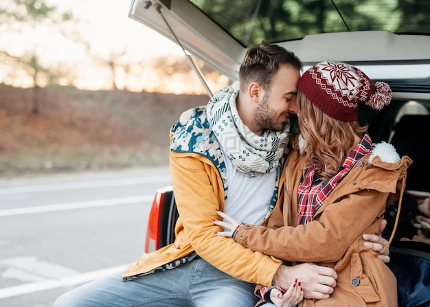 Młoda para mężczyzny i kobiety, ubrana w ciepłe ubrania, siedząca na bagażniku samochodu, przytulanie w zimowy dzień
