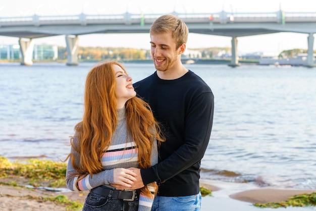 Młoda para mężczyzny kobieta z długimi rudymi włosami pochodzenia kaukaskiego w zwykłych ubraniach stoi na t
