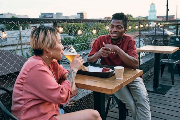 Młoda para międzykulturowa relaksuje się przy stole w kawiarni na świeżym powietrzu