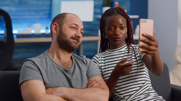 Młoda para międzyrasowa korzystająca z wideokonferencji online