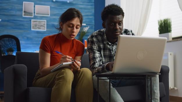 Młoda para międzyrasowa obliczająca podatki i papierkową robotę