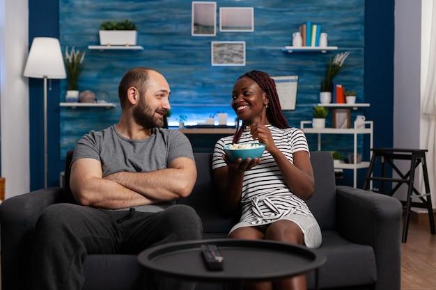 Młoda para międzyrasowy śmiejąc się i rozmawiając na kanapie. pov wieloetnicznych partnerów uśmiechających się podczas jedzenia popcornu i omawiających film w telewizji. ludzie rasy mieszanej cieszący się wolnym czasem