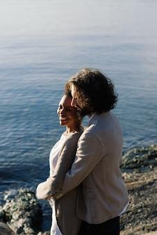 Młoda para międzyrasowych dorosłych na plaży, mężczyzna rasy kaukaskiej i african american kobieta w ubranie, ciesząc się letnim dniem na brzegu morza
