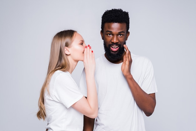 Młoda para mieszana opowiadająca sobie sekret na białej ścianie
