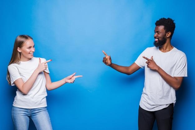 Młoda para mieszana wskazała na siebie na białym tle na niebieskiej ścianie