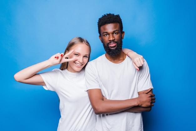 Młoda para mieszana z gestem pokoju odizolowana na niebieskiej ścianie