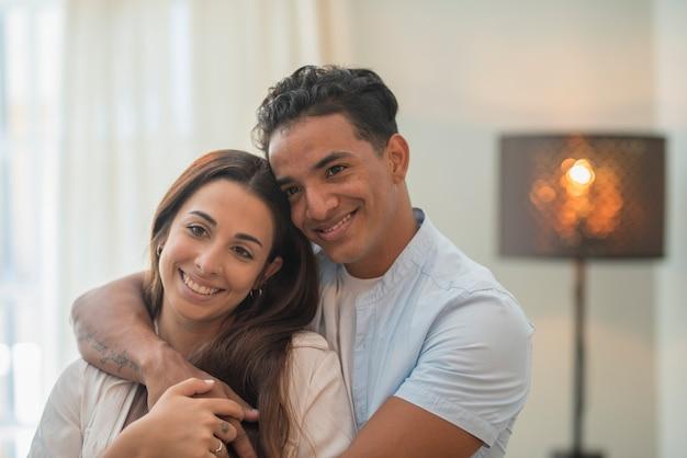 Młoda para milenijnych międzyrasowych przytula się z miłością w domu w salonie - związek z czarnym chłopcem i kaukaską dziewczyną razem stojąc i obejmując się patrząc na siebie - koncepcja życia i domu