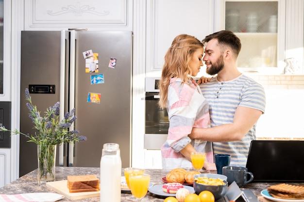 Młoda para miłości, obejmując w kuchni