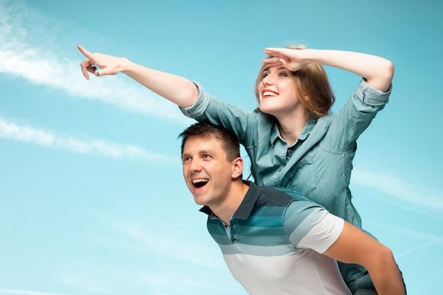 Młoda para miłości uśmiechnięta pod błękitnym niebem i odwracająca wzrok