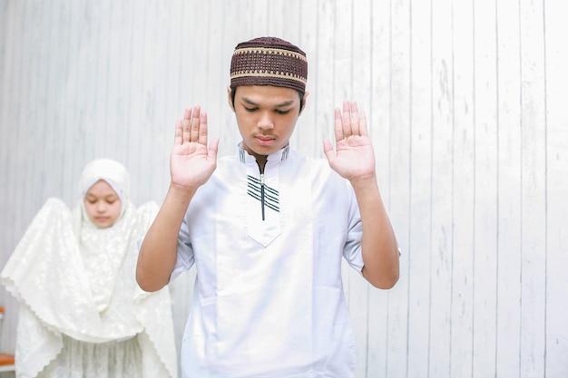 Młoda para muzułmanin robi salat wraz z podniesieniem ręki lub pozą takbiratul ihram