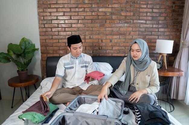 Młoda para muzułmanów wspólnie przygotowuje bagaż