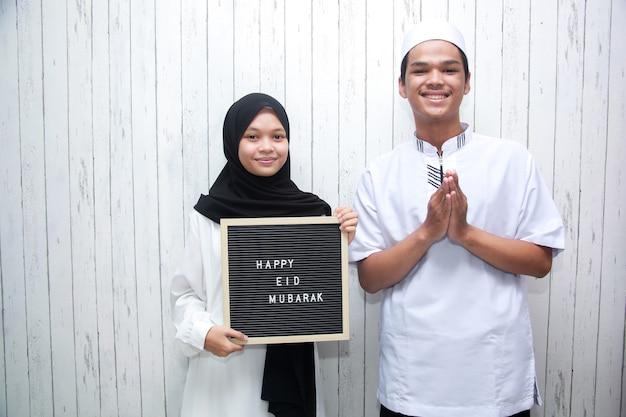 Młoda para muzułmańska robiąca pozę powitalną i trzymająca tablicę z literami mówi happy eid mubarak