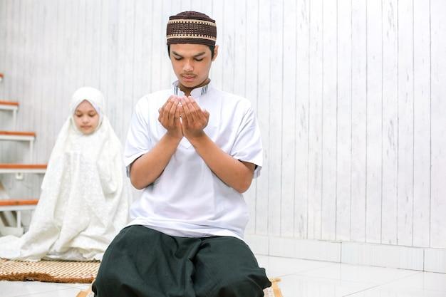Młoda para muzułmańskich modląc się razem w domu