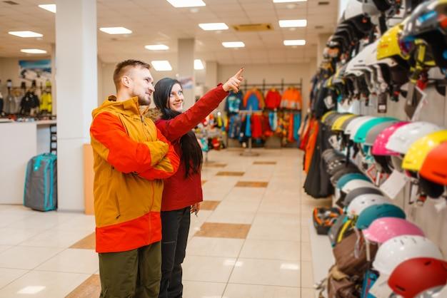 Młoda para na gablocie wybierająca kaski na narty lub snowboard, widok z boku, sklep sportowy.