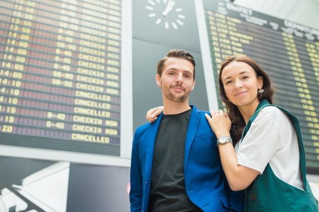 Młoda para na lotnisku międzynarodowym patrząc na tablicę informacyjną lotu