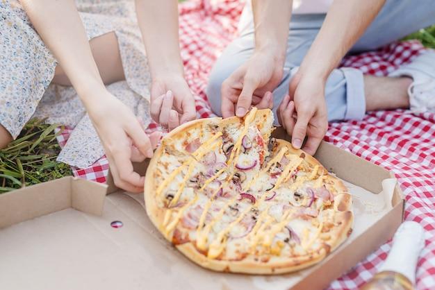 Młoda para na pikniku jedząca pizzę?