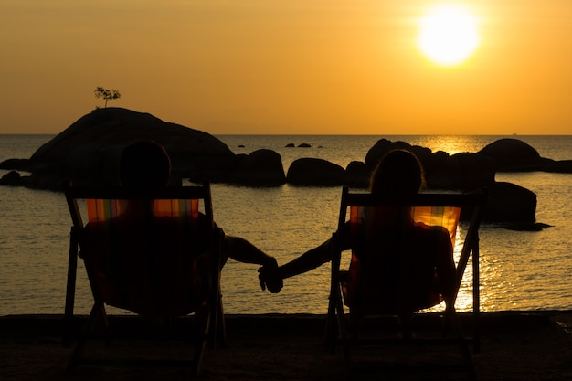 Młoda para na plaży hamaki, trzymając się za ręce, podziwiając wspaniały zachód słońca nad morzem ze skałami nad wodą w tle.