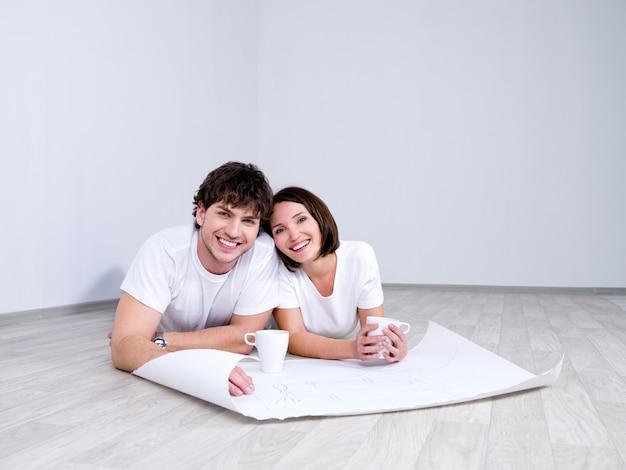 Młoda para na podłodze z planem nowego pokoju
