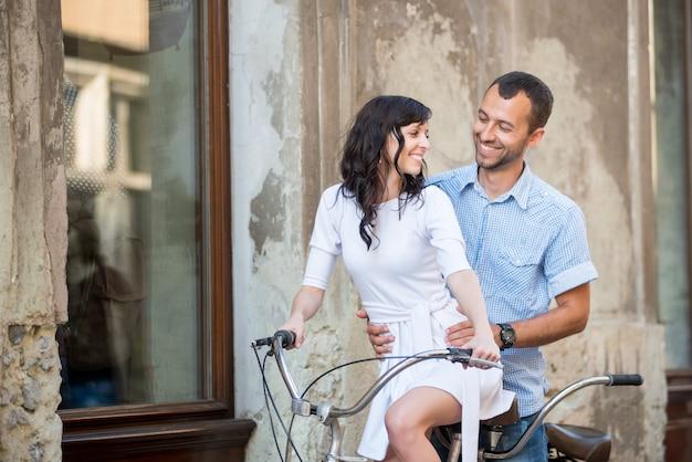 Młoda para na retro rower tandemowy na ulicy miasta