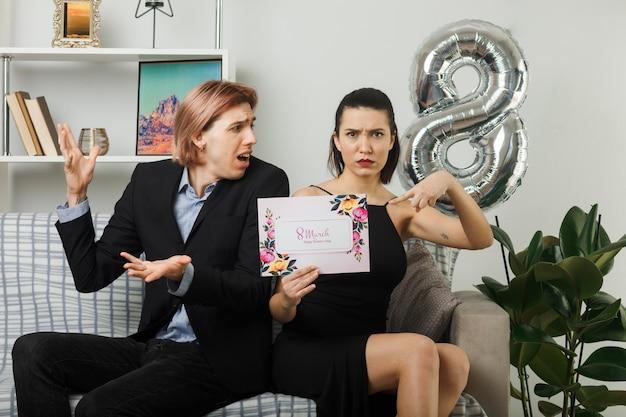 Młoda para na szczęśliwy dzień kobiet trzyma i wskazuje na pocztówkę, siedząc na kanapie w salonie