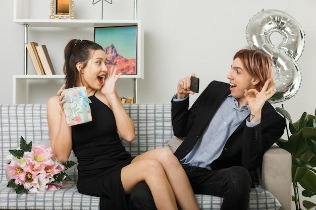 Młoda para na szczęśliwy dzień kobiet, trzymając prezent siedzący na kanapie w salonie