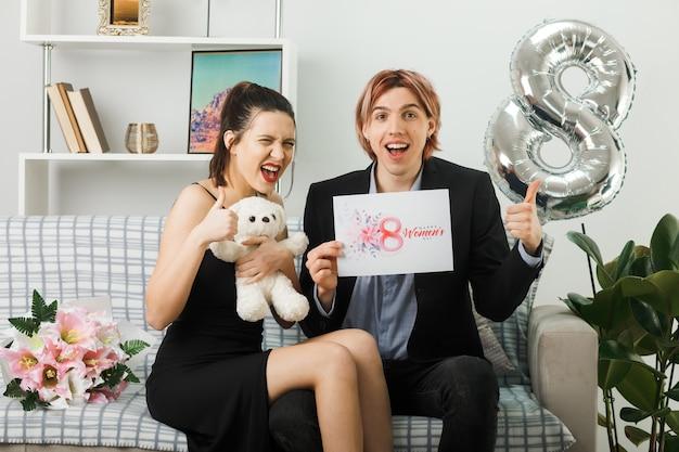 Młoda para na szczęśliwy dzień kobiet z misiem i pocztówką, siedząc na kanapie w salonie