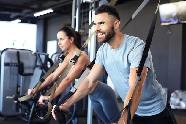 Młoda para na treningu ciała z trx w siłowni.
