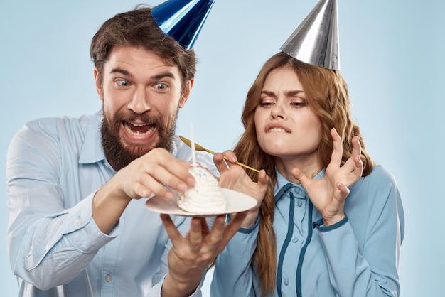 Młoda para na urodziny z babeczką i świeczką w świątecznych czapkach