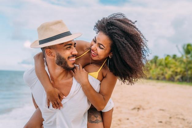 Młoda para na wakacjach na plaży, szczęśliwy uśmiechnięty mężczyzna nosić kobietę z powrotem nad morzem