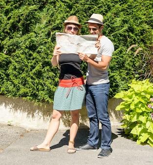 Młoda para na wakacjach, patrząc na mapę