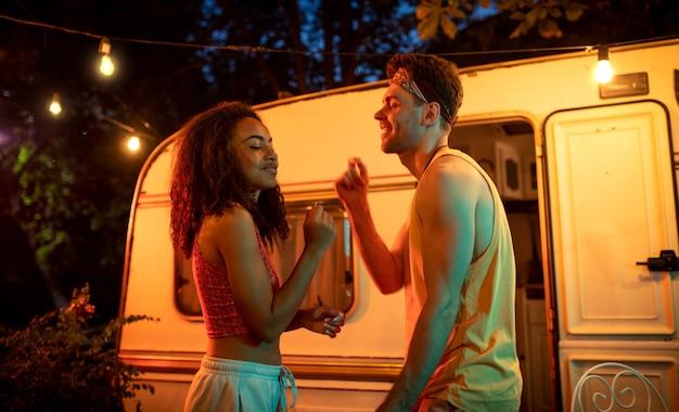 Młoda para na wakacjach z kamperem. tańczyć w nocy na świeżym powietrzu. koncepcja o podróżach i stylu życia na wakacjach