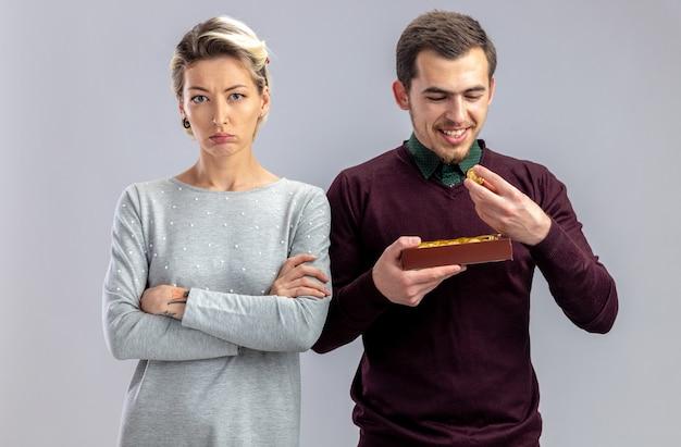 Młoda para na walentynki niezadowolona dziewczyna stojąca obok faceta z pudełkiem cukierków na białym tle